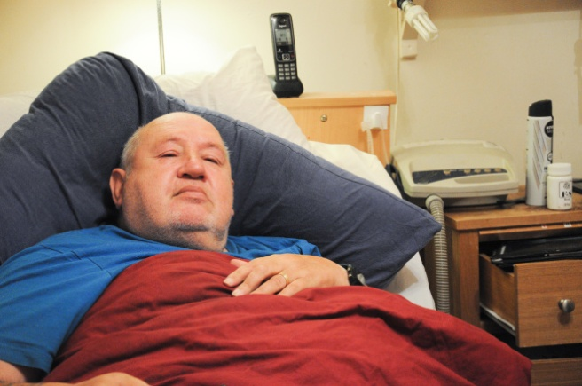 Robert, a disabled man in his 60s, in bed.